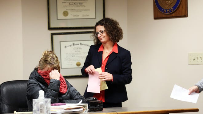 Janice Roberts, hiding her face next to defense attorney Robin Runstein, pleads guilty at Marion County Courthouse to stealing tens of thousands of dollars from Oregon RISE, the nonprofit organization she led.