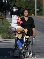 Crystal Wright visits the memorial for her son, Charles Wright, on the corner of 4th Street and Rowland Avenue.