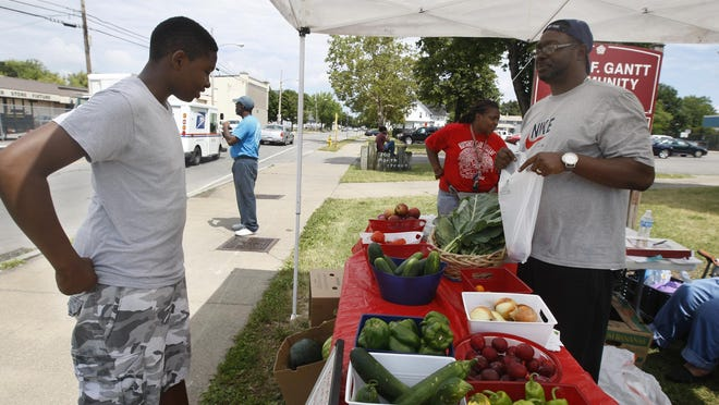 File photo: Ronnie Johnson, a volunteer with Bridges to Wellness, helps Eric Moye, 12, at a farm stand at Draper and North streets.
