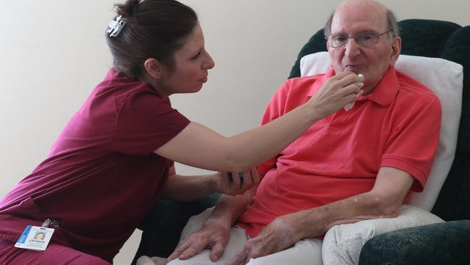 Christine Gianvecchio, senior health home aid for Rochester Regional Health Services, wipes some yogurt off Sam Macaluso's mouth after he had a few bites. She had been feeding him in his Irondequoit home after helping him get dressed for the day.