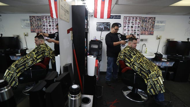 Roniel Cruz shaves and styles Jose Torres's hair at  Roniel's Barber Shop on North St.  Cruz has owned the shop for around three years.
