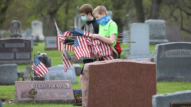 Luke and Kyle Otto, brothers, grab a flag out of their pile, to put on veterans' graves that don't have flags at Holy Angels Cemetery in Scottsville on Saturday, May 16, 2020. Troop 140 and Pack 140 with Boy Scouts BSA put flags and veteran markers on the graves in conjunction with American Legion Smith-Warren Post 367. Post 367 is also the Troop's sponsor.