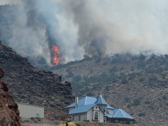 The Perry Fire is seen burning just above a home at