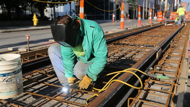 Matt Walker, with Prus Construction, welds the steel along 12th street in Over-The-Rhine for the streetcar.