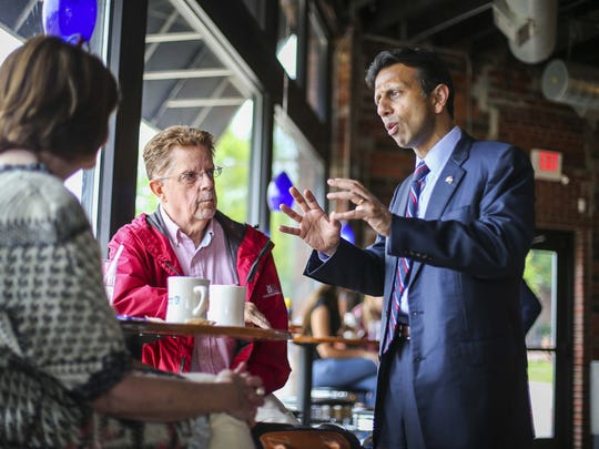 Gov. Bobby Jindal, a potential Republican presidential candidate, visits with Steve Warner of Des Moines (red jacket) at Smokey Row Coffee in Des Moines, Iowa, Monday June 15, 2015.
