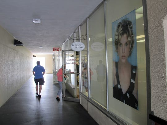 A patron enters Distinctive Hair Salon on April 6, 2017, in Naples Plaza. The longtime local hair salon is closing this week to make way for a redevelopment project.