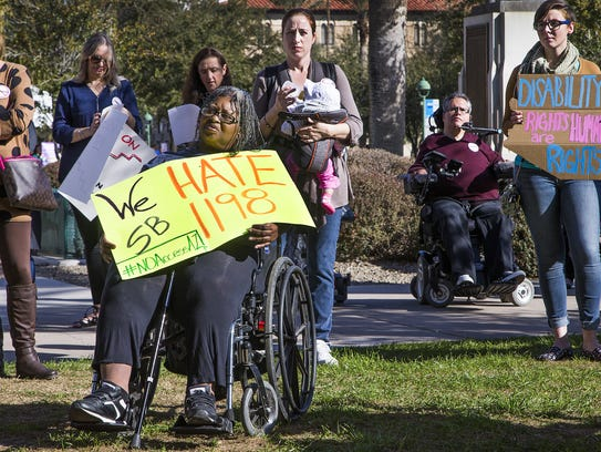 """Annette Denny, 65, of Phoenix holds a """"We Hate SB1198"""""""