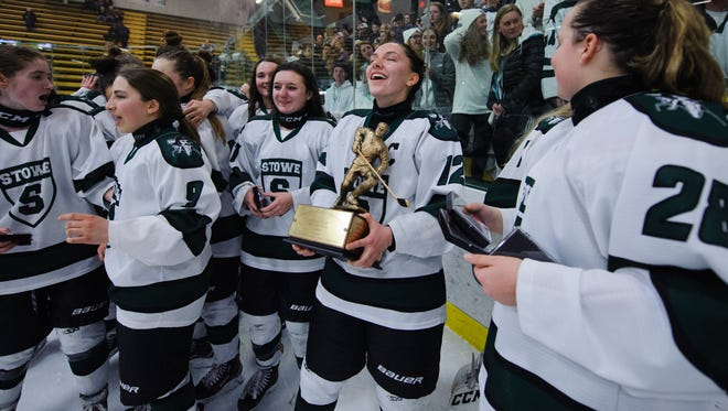 Stowe's Darian Dubie (12) holds the trophy as Stowe celebrates the championship during the Vermont state division II girls hockey championship game between the Missisquoi Valley Union Thunderbirds and the Stowe Raiders at Gutterson Field House on Monday night March 12, 2018 in Burlington.