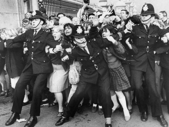 Beatles fans try to break through a police line Oct. 26, 1965, at Buckingham Palace in London where group members were due to receive Member of the British Empire awards from the queen. Two months earlier, the group performed in Bloomington.