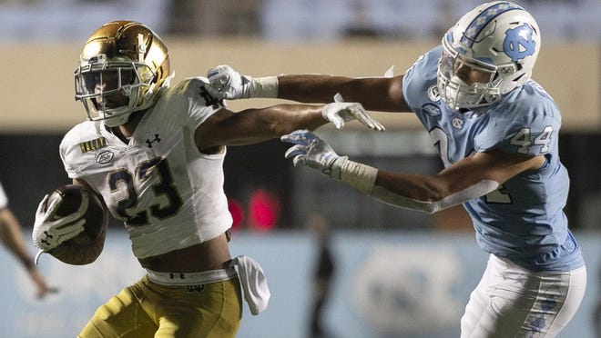 Notre Dame running back Kyren Williams, left, fends off North Carolina linebacker Jeremiah Gemmel in the fourth quarter of Friday's game at Kenan Stadium.