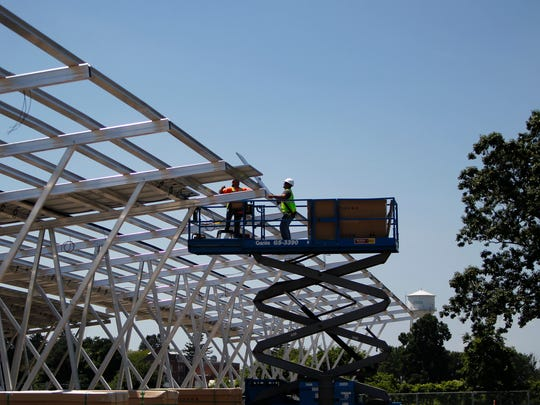 Crews install solar panels above newly created parking bays Thursday at lot 89 on the campus of Michigan State University.  There will be more than 40,000 solar panels put up once the project is complete.