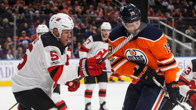 New Jersey Devils' Dalton Prout (5) hits Edmonton Oilers' Patrick Maroon (19) with his stick during second-period NHL hockey game action in Edmonton, Alberta, Friday, Nov. 3, 2017. (Jason Franson/The Canadian Press via AP)