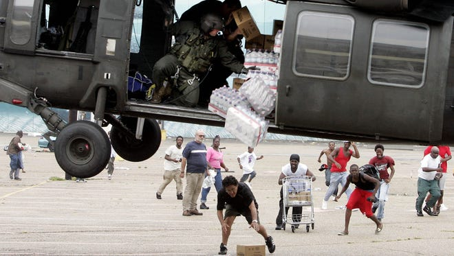 A military helicopter makes a food and water drop to survivors of Hurricane Katrina near the  Convention Center in New Orleans, Thursday, Sept. 1, 2005.
