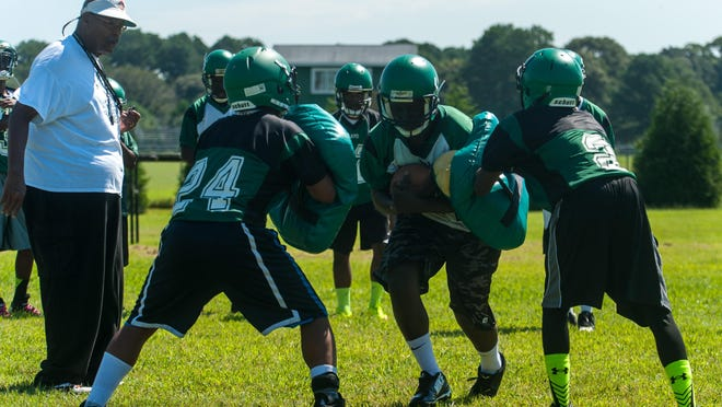 A Parkside running back pushes through blocking pads on the second day of practice.