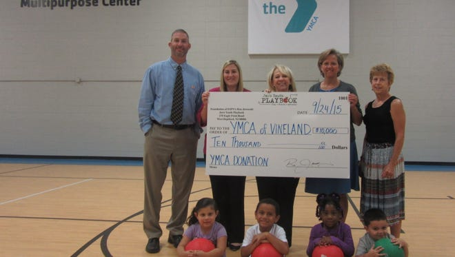 Representatives of the YMCA of Vineland and Jaws Youth Playbook celebrate a donation to the YMCA's capital campaign: (standing, from left) Bob Crouthamel, director for youth and family for the YMCA of Vineland; Trish Yerkov, Liz Jaworski and Sara McCollough of the Jaws Youth Playbook; and Christine Ward Garrison of the YMCA; and (seated, from left) with new kick balls that the guests donated, Ian Cedeno Barrero, Aiyana Milbourne, Hayden Smith and Jessiana Morales, all from the Vineland area.