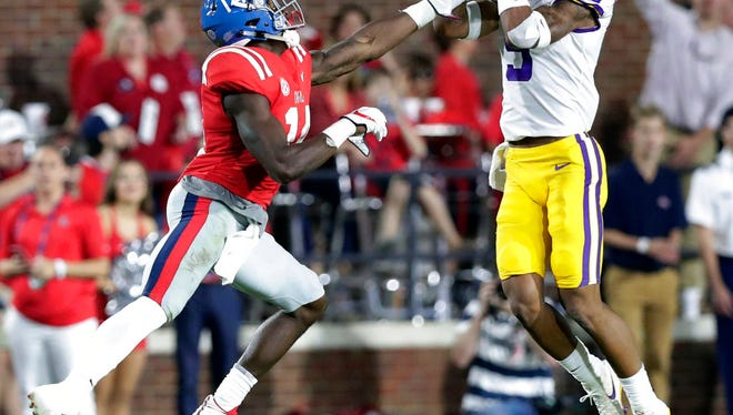 LSU safety Grant Delpit (9) intercepts a pass intended for Mississippi wide receiver D.K. Metcalf (14) in the first half of an NCAA college football game in Oxford, Miss., Saturday, Oct. 21, 2017. (AP Photo/Rogelio V. Solis)
