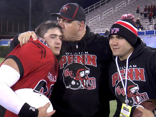William Penn coach Marvin Dooley kisses son Brandon while son Nick watches after the Colonials won the 2014 Division I state championship over Middletown.