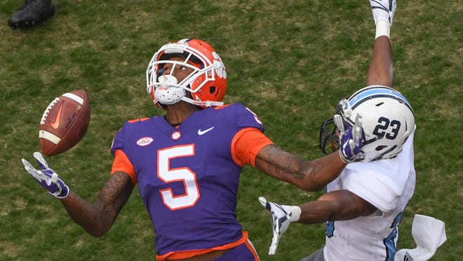 Clemson wide receiver Tee Higgins (5) reaches for a pass near The Citadel defensive back Tyus Carter(23) during the second quarter in Memorial Stadium at Clemson on Saturday.