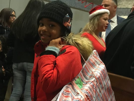 With a bag of toys in hand, Nariyah Mason, 7, smiles during the Bloomfield Police Department's annual toy distribution on Thursday, Dec. 21, 2017.