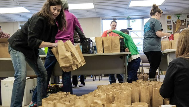 Hilary Parkinson, left, Volunteer and Garden Resource Coodinator for the Greater Lansing Food Bank, moves around some of the bags filled with garden seeds as volunteers fill them Saturday, January 14, 2017.