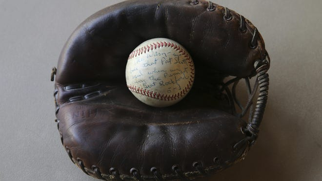 """Lois Youngen's 10 inch baseball and a catchers glove that was used to catch a perfect game while playing professional baseball for 4 years after WWII, sits on display at the Westminster Presbyterian Church in Eugene, Ore. on Sa Jan. 13. Her story was told in the film """"A League of Their Own."""""""