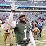 New York Jets quarterback Michael Vick (1) smiles as he leave the field after an NFL football game against the Pittsburgh Steelers Sunday, Nov. 9, 2014, in East Rutherford, N.J. The Jets won the game 20-13.