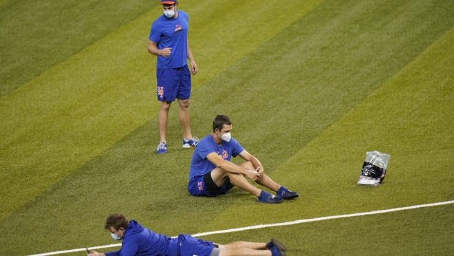 New York Mets players sit on the field before a baseball game against the Miami Marlins, Thursday, Aug. 20, 2020, in Miami. Major League Baseball says the Mets have received two positive tests for COVID-19 in their organization, prompting the postponement of two games against the Marlins.