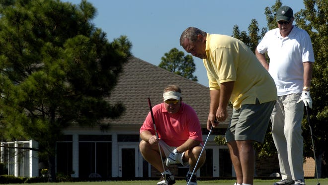 Doug Permenter, left, and Buddy Scruggs watch teammate Greg Permenter sink a putt at Tiger Point Country Club.
