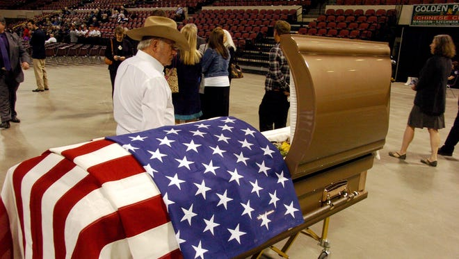 An unidentified mourner pays tribute to former U.S. Sen. Conrad Burns during the funeral service Friday for the three-term lawmaker at the Metra Park Arena in Billings.