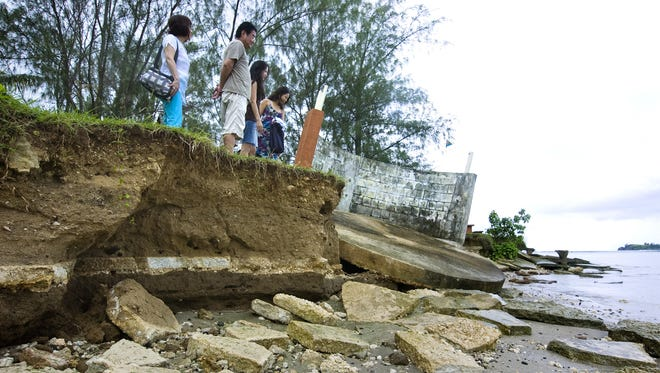 In this Sept. 23, 2009, file photo tourists examine at the eroding shoreline of Nimitz Beach in Agat.