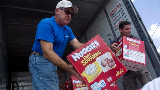 Volunteers Jim Luther, left, and Chad Thomas help unload a truck load of Huggies diapers to the Destiny Diaper Bank. The organization is in need of volunteers to help support the group's daily activities.