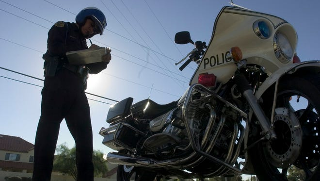Mesa police Officer Stefan Martinez writes a ticket to a motorist caught speeding in September 2005.