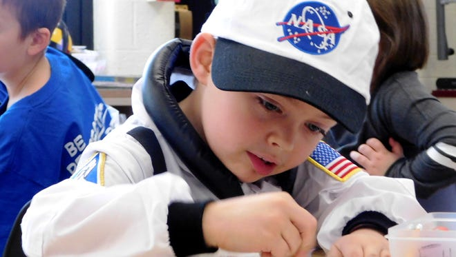 Kindergartner Ethan Langlois, fully dressed in his NASA outfit for Career Day, concentrates on a worksheet Thursday morning in the class of Clyde Elementary School teacher Rhonda Miller.