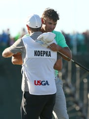 Former Florida State golfer Brooks Koepka celebrates with his caddie Richard Elliott after winning the U.S. Open golf tournament.