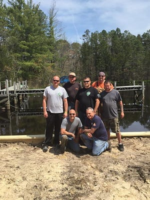 (Kneeling, from left) Brett Scarpa and Lou Tramontana; and (standing, from left) John Hendershott, Gary Galloway, Todd Birdsall, Terry McManus and James Muirheid recently volunteered at the YMCA of Vineland's Camp Merrywood to repair its water recreation area. For camp information, call (856) 691-0030.