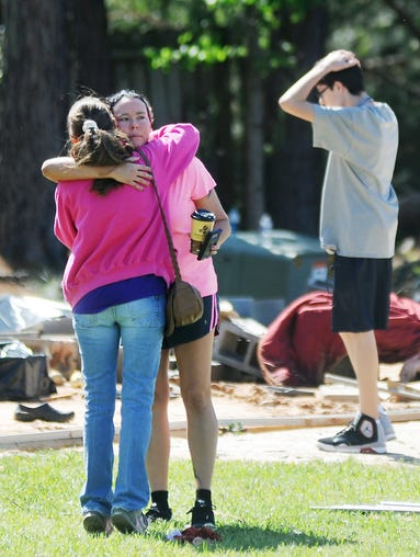 Cristal Palmer, center, gets a hug from her landlord, Denise Sullivan, as Palmer's son Payton Dye gets his first look at the family's overturned and completely destroyed mobile home at Highlands trailer park in Pearl on Wednesday.  On Monday, the family heeded the pleas of a friend to leave the trailer for a more secure location just minutes before a powerful tornado swept through the area, leaving destruction in its wake.