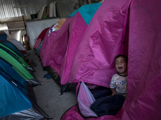 A Honduran migrant toddler who is traveling with a caravan of Central American migrants cries inside a tent set up at the Juventudes 2000 shelter in Tijuana, Mexico, on Wednesday. The caravan of mainly Central American migrants are planning to request asylum, either in the United States or Mexico.