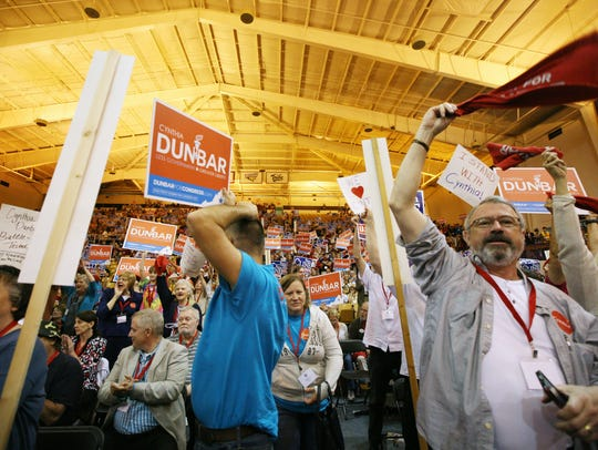Supporters of Cynthia Dunbar wave signs at the 6th