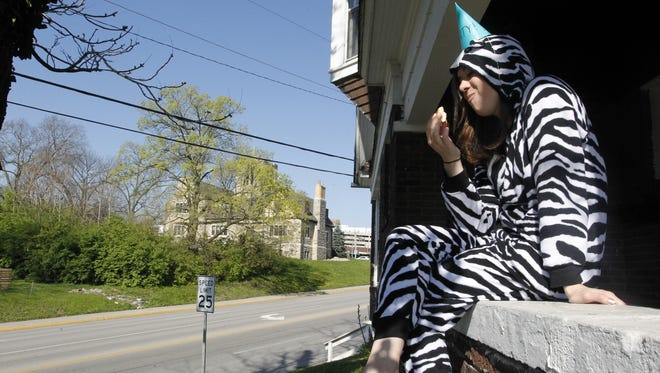 Purdue junior Katie Blink eats a sandwich Saturday morning on the ledge of a house overlooking State Street. Blink and her friends were celebrating Grand Prix on April 23, 2016.