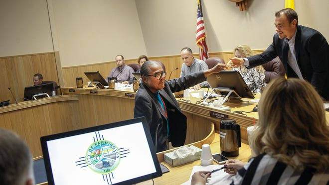 "Shiprock Chapter President Duane ""Chili"" Yazzie shakes hand with Farmington City Councilman Sean Sharer and other members of the City Council Tuesday at City Hall."