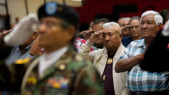 Vietnam veterans salute during the presentation of colors at a Vietnam veterans pinning ceremony at Navajo Technical University in Crownpoint on Sept. 22. Programs for Navajo veterans will receive additional funding under legislation recently enacted by Navajo lawmakers.