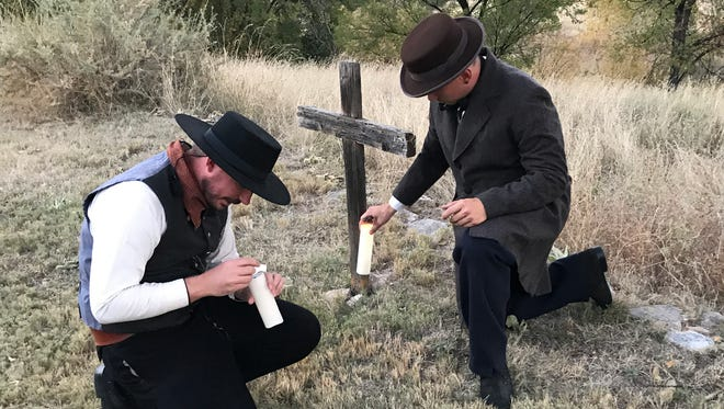 Regional Site Manager Tim Roberts and staff member Kenneth Walter set the candles near the grave of John Tunstall for the tour.