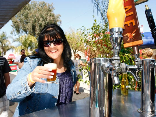 Deanea Lizardo, pictured, enjoys a Pacific Ridge Pale Ale by Anheuser Bush from the Sequoia Beverage Company booth during a festival at the Tulare County Fairgrounds.