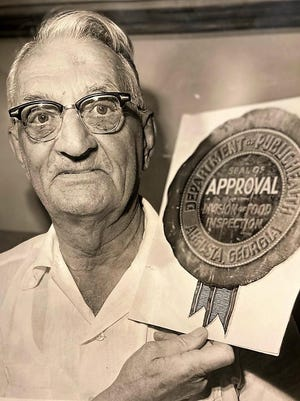 Dr, Archie L. Haggerty shows of the seal he devised for restaurant inspections.