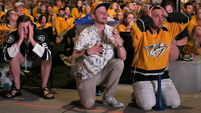 Fans Brady Trapnell, left, Ian Yocum and Mo Ayrab watch TV during the third period as the Jets score on Predators during game 7 in Nashville on Thursday, May 10, 2018.
