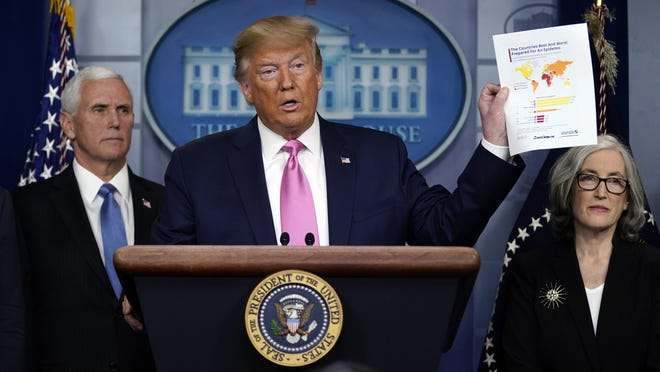 WASHINGTON -- President Donald Trump, with members of the President's Coronavirus Task Force, holds a paper about countries best and least prepared to deal with a pandemic, during a news conference in the Brady Press Briefing Room of the White House on Feb. 26.
