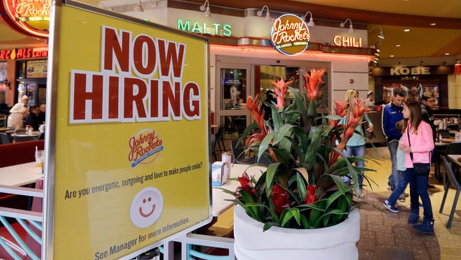 In this Feb. 9, 2016, file photo, a restaurant posts a sign indicating they are hiring, in Miami.
