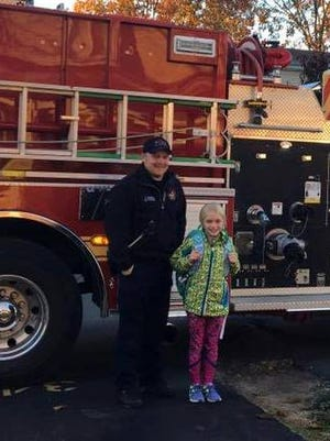 South Lyon Fire Lt. Tim Wilson with Lillian Swegle, whose winning coloring entry won her a ride to school on a fire engine.