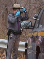 A New York state trooper photographs possible evidence along Route 116 across from Windswept Farm on Titicus Road in North Salem as they investigate the killing of Lois Colley Nov 10, 2015.