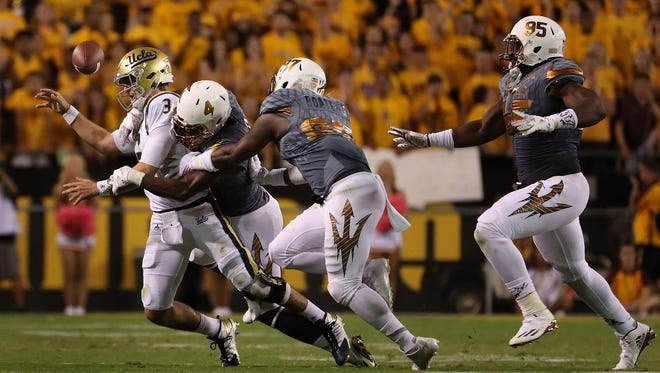 UCLA quarterback Josh Rose fumbles the football as he is tackled by Arizona State defensive lineman Koron Crump  at Sun Devil Stadium on October 8, 2016 in Tempe.
